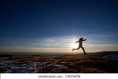 silhouette of man running in sunset sky