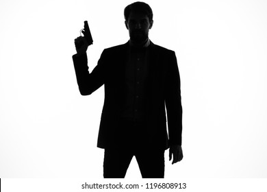 silhouette of a man in the shadow with a gun