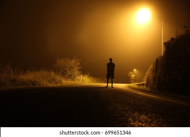 The silhouette of a man in shorts, standing in the middle of the road on a misty night. The glare of the street light against the fog sets a creepy mood. Concept of thieves, rapist and killers roaming