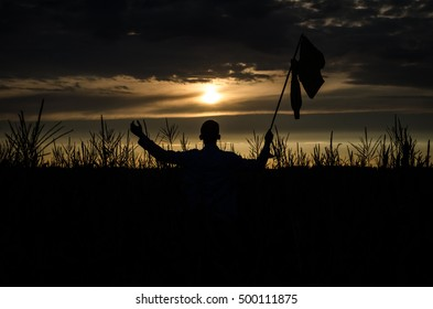 silhouette of man in shorts and a t-shirt in a cornfield with hand-made yellow flag caught with hands and show the direction with hand at sky cloud background