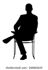 Silhouette of a man sitting in a modern armchair with one leg over his knee.