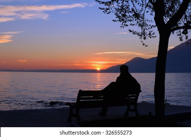 silhouette of a man sitting on a bench on lakeside, looking at sunset and meditating