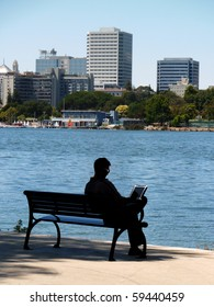 Silhouette of a man sitting on bench by Lake Merritt using laptop