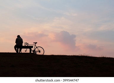 Silhouette a man  sitting on the branch with his bicycle after sunset