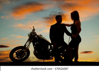A silhouette of a man sitting on his bike holding on to his woman.
