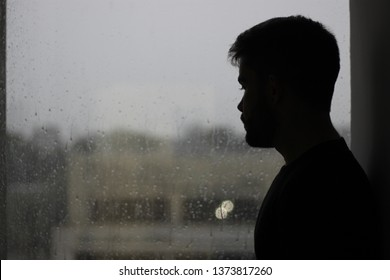 silhouette of a man sitting in the window with rain in mood of sadness and depression