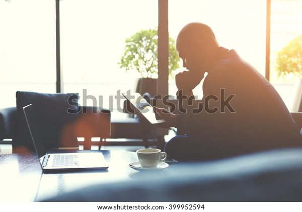 Silhouette of a man skilled managing director is analyzing the activities of the company by using touch pad and net-book. Thoughtful male economist is reading news in network via digital tablet