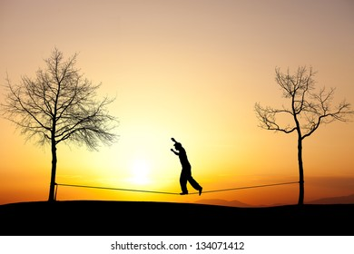 silhouette of man slacklining in sunset