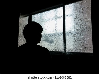Silhouette of man smoking against window at his room.