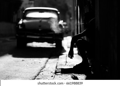 Silhouette of man smoking on street of Havana with old car in a background, Cuba