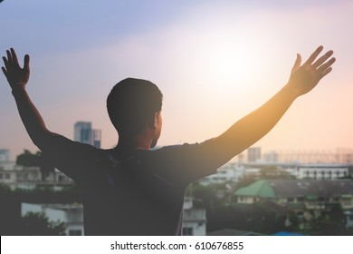 The silhouette of a man spread his arms wide as a winner or freedom on a landscape background.