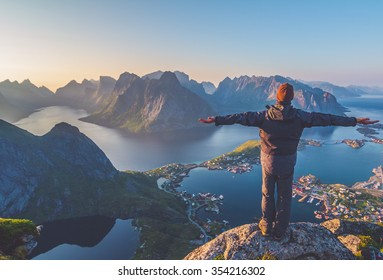 Silhouette of the man spreading arms and standing high on rock like the Statue of Christ the Redeemer looking at breathtaking view over small village,mountain landscape, sea during sunset in Norway