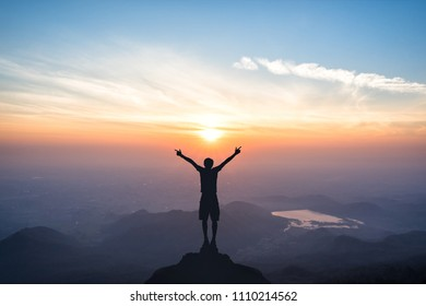 Silhouette of man spreading hand and enjoy great sunrise above the mountain valley and morning mist.