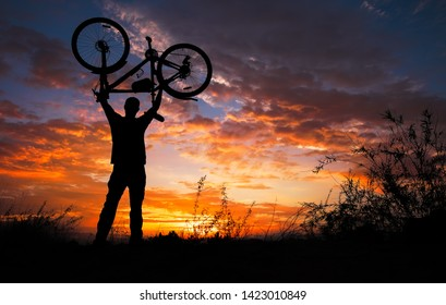Silhouette the man stand in action lifting bicycle above his head on the meadow with sunset