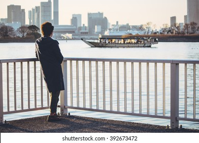 Silhouette of Man stand alone on bridge look to boat in river