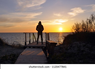 The silhouette of man standing alone at the beach, concept of lonely, sad, depressed, thoughtful. Thinking about meaning of life