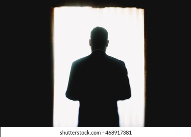 Silhouette of a man standing before a bright window in the dark room