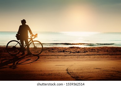 Silhouette a man standing with bicycle on the beach in summer.