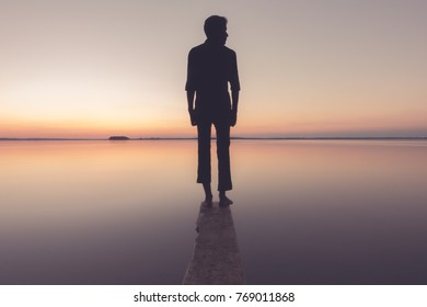 silhouette of a man standing by the lake