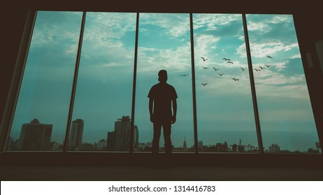 Silhouette man standing in front of window