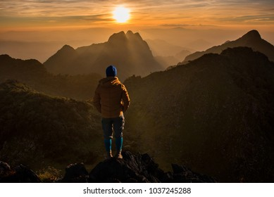 Silhouette of the man standing and looking high and beautiful mountain withsunset
