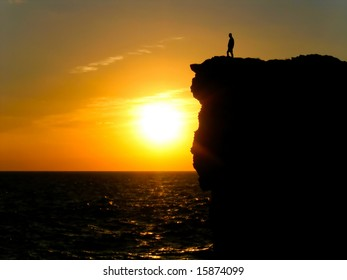 Silhouette of a man standing on an Atlantic Ocean cliff watching the sunrise.