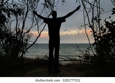 Silhouette of a man standing on the background of the sunset and the sea with arms outstretched