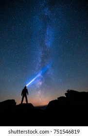 Silhouette of man standing on edge of cliff with lighter and looking into starry sky