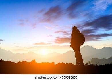 silhouette of man standing on the mountain at sunrise,conceptual scene