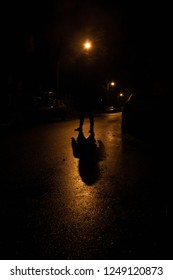 Silhouette of a man standing on the road illuminated by a street lamp, has a vigilante/sinister feel.