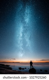 Silhouette of a man standing on a rock by a sea and looking at sunset and stars of the milky way
