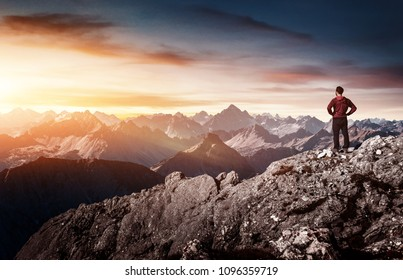 Silhouette of man standing on rock while admiring view in mountains at sunset