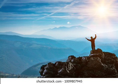 Silhouette of a Man standing on a stone cliff, success and victory in the mountains