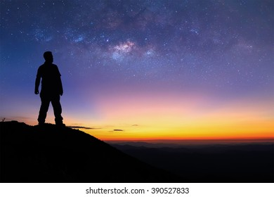 Silhouette of man is standing on top of mountain and enjoy to see the milky way before sunrise. Young tourist stand on the hill with colorful night sky on background.