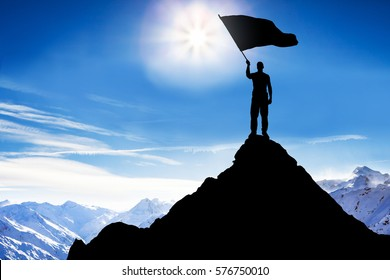 Silhouette Of A Man Standing On Top Of The Mountain Peak Waving Flag