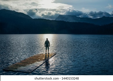 Silhouette man standing on the wooden raft on the blue lake. Cloudy mountain in the back with the evening light in nature landscape. Reflexion on the raft. Black Lake, Montenegro, Durmitor