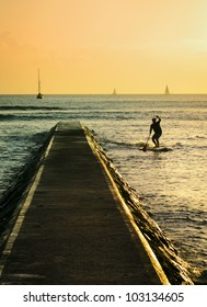 A silhouette of a man stand-up paddling at sunset in Waikiki, Hawaii.