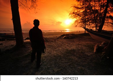 silhouette of a man staring at the beach see people having fun with the weather sunset