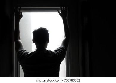 Silhouette of man staring the window of his room. He think something about his life, negative thinking or he need to suicide