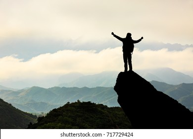 Silhouette of the man success on the peak of mountain,Sport and active life