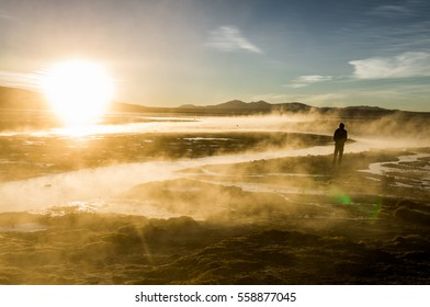 The silhouette of a man in the sunrise light surrounded by vapor