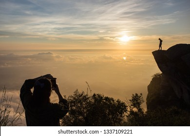Silhouette man taking photo on top of a Mountain.