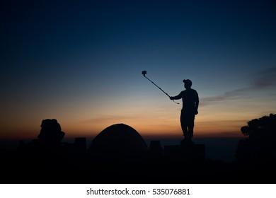 Silhouette of man taking a selfie on mountain in sunrise.