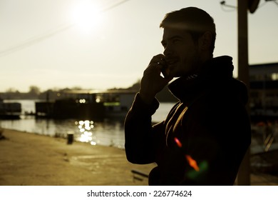 Silhouette Of A Man Talking On Smart Phone Near River