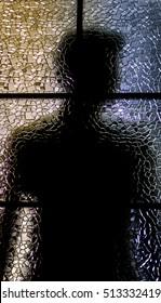 Silhouette of the man through door glass