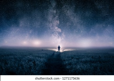 A silhouette of a man with a torch in a field, looking at lights on the horizon on a moody misty night. With a galaxy of stars overhead.