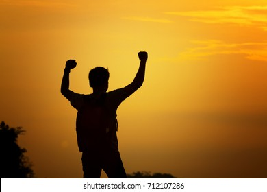 silhouette of man travel show arm up for achievements successful and celebrating success with sunrise