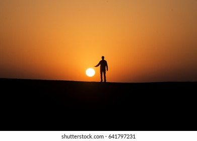 silhouette of a man trying to catch the sun due to juxtaposition technique during the sunset