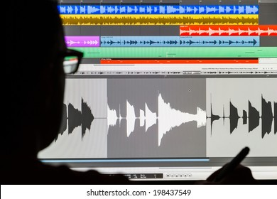Silhouette of a man using a Digital Audio Workstation to edit sound and arrange music