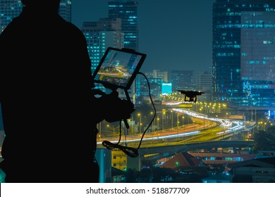 Silhouette of Man using drone to monitor the city  night traffic.